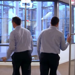Still from video showing 2 identical employees walking through door