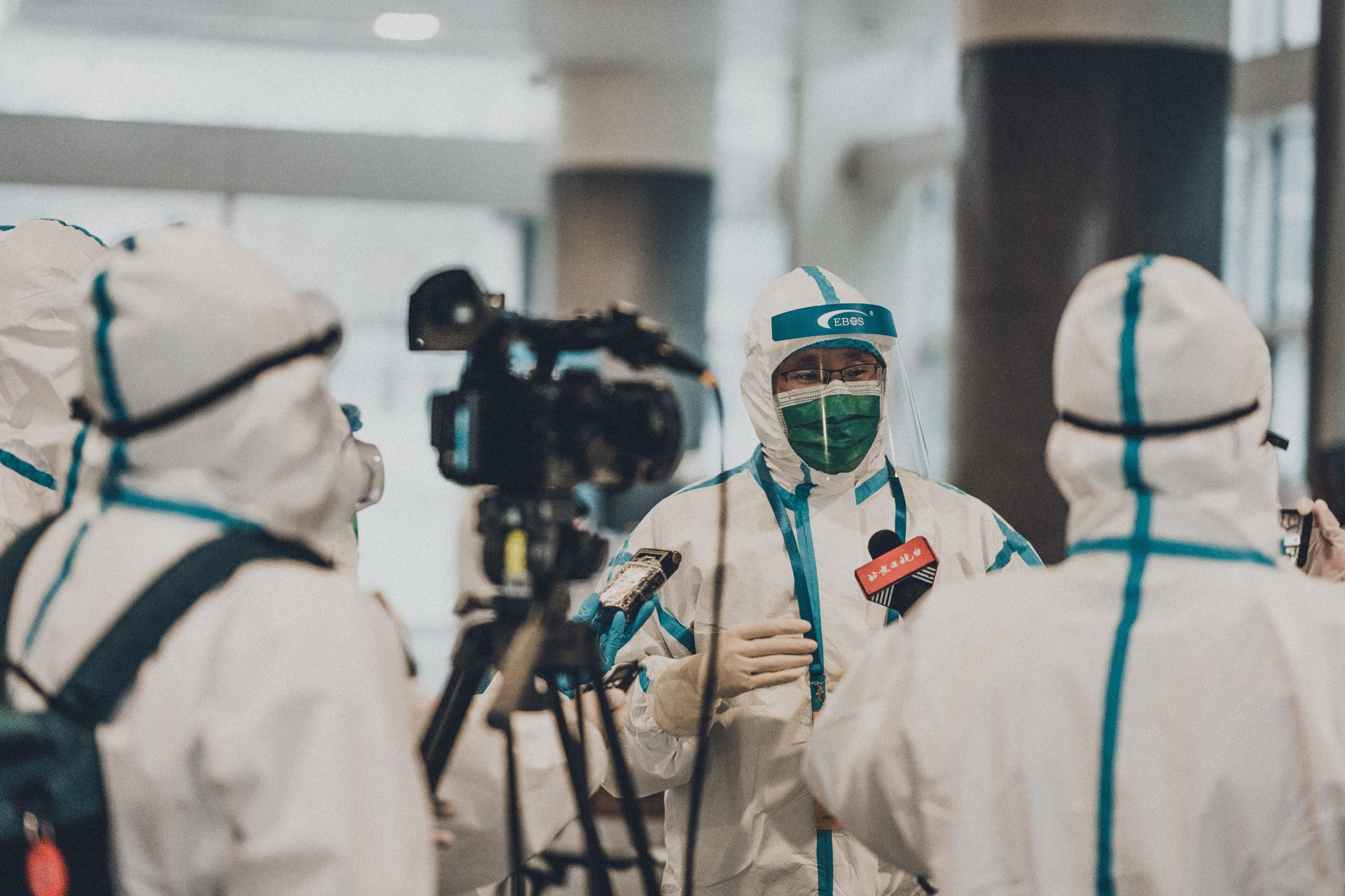 People in PPE being interviewed on camera